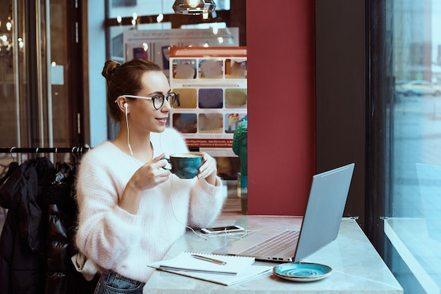 Woman entrepreneur working from cafe and talking on mobile phone