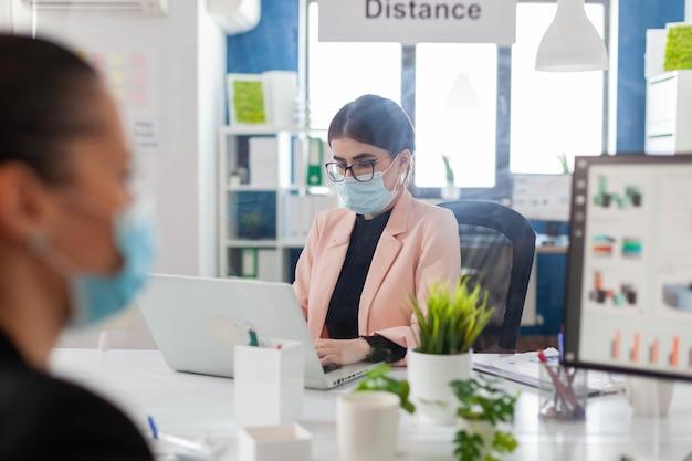 Женщина-предприниматель работает на ноутбуке в новом обычном офисе с коллегами, которые держат социальную дистанцию за пластиковой упаковкой, носят лицевую маску в качестве меры безопасности во время вспышки гриппа корнавируса.