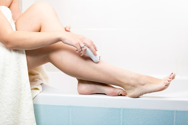 Woman epilating legs at bathroom after having shower