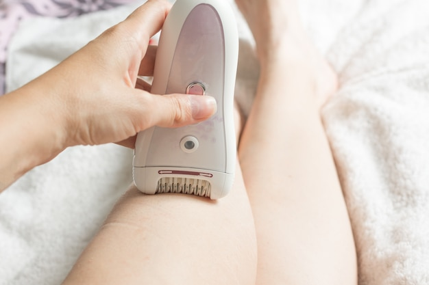 Woman epilating legs at home by epilator.