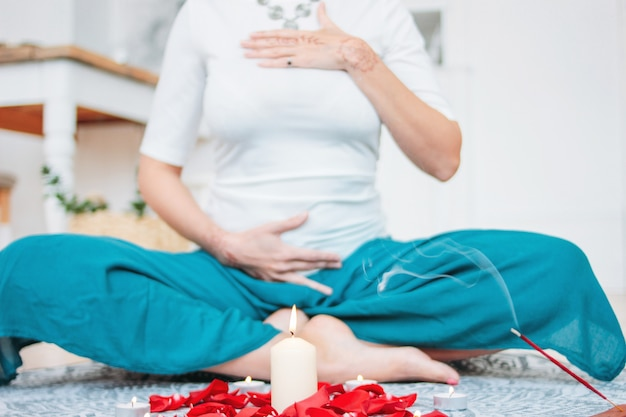 Woman in ethnic costume practicing yoga in front of candles and red rose petals