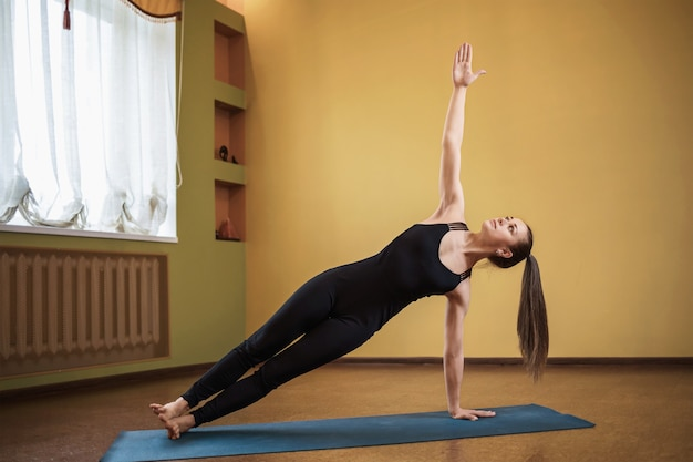 Woman of european appearance practicing yoga performs the exercise vasishthasana