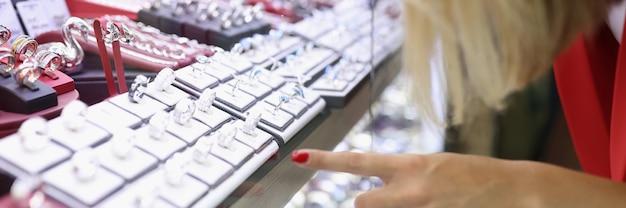 Женщина рассматривает и выбирает украшения в магазине.
