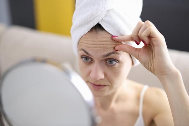 여성은 거울에서 이마 주름을 검사합니다. 깊은 주름을 예방하는 방법 개념