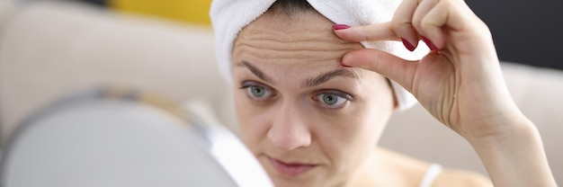 여자는 깊은 주름 개념을 방지하는 방법을 거울에 그녀의 이마 주름을 검사