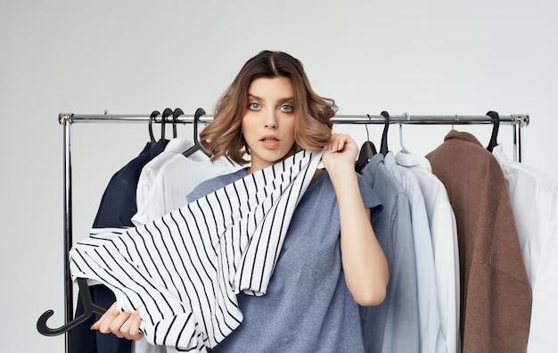 女性がワードローブの買い物で服の近くに縞模様のtシャツを調べる