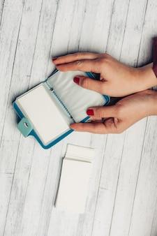 Женщина рассматривает прозрачные листы в держателях визиток на деревянном столе