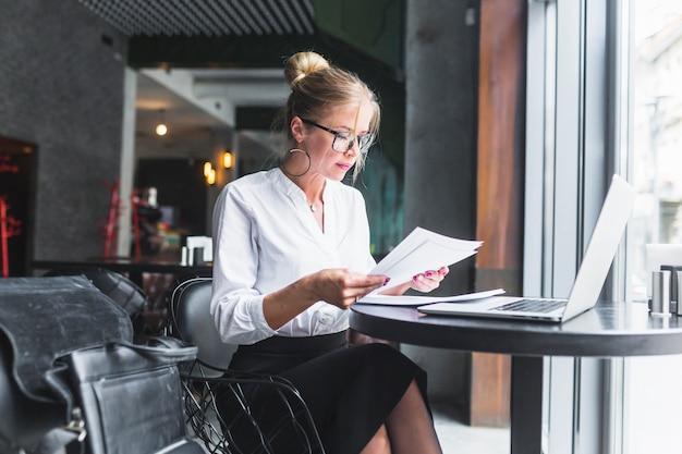 Woman examining document in restaurant