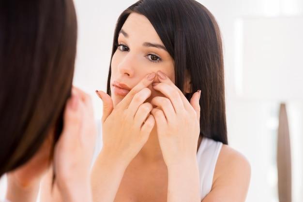 Женщина изучает лицо. красивая молодая женщина, изучая ее лицо, глядя в зеркало