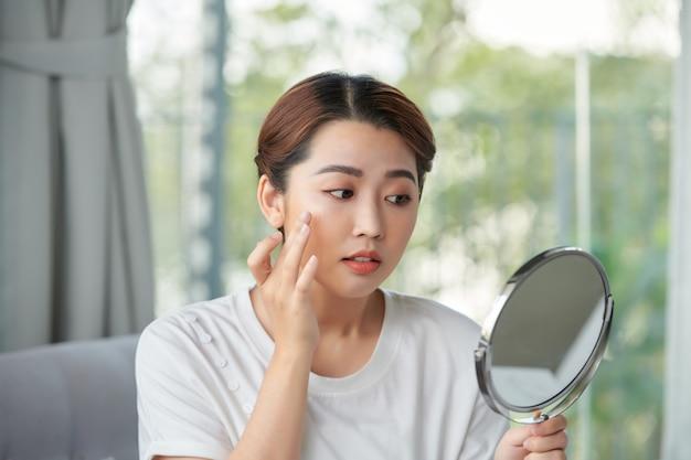 거울에 그녀의 얼굴을 검사하는 여자, 문제가 여드름이 나는 피부 개념