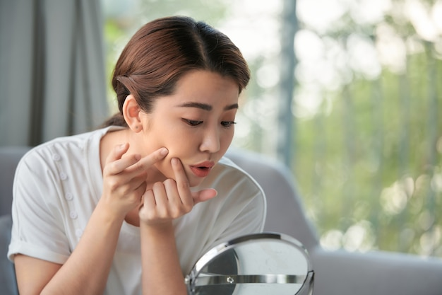 Woman examining her face in the mirror, problematic acne-prone skin concept