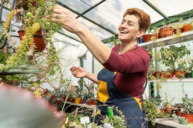Женщина рассматривает свои зеленые растения и восхищается их красотой.