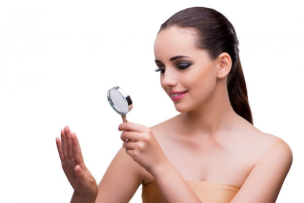 Woman examining her nails with magnifying lens