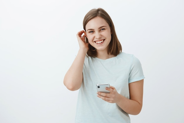 Woman exchanging numbers with cute guy on festival. charming friendly-looking young girl flicking hair behind ear flirty and laughing while gazing holding smartphone against gray wall