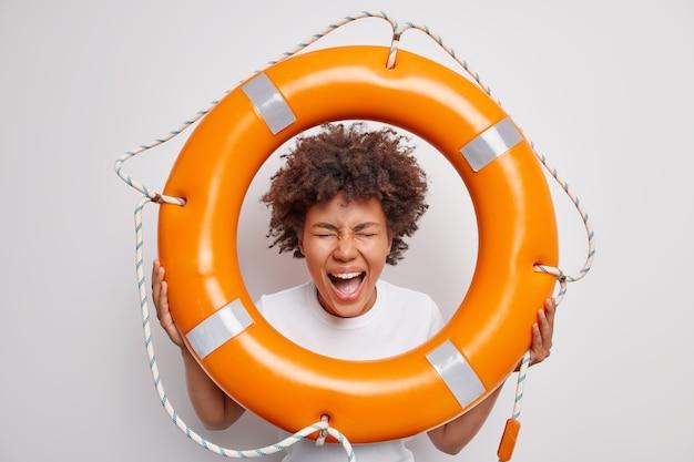 Женщина восклицает с широко открытым ртом держит спасательный круг наблюдает за людьми на воде, чтобы предотвратить несчастные случаи, позирует со спасательным снаряжением на белом, готовым спасти вас