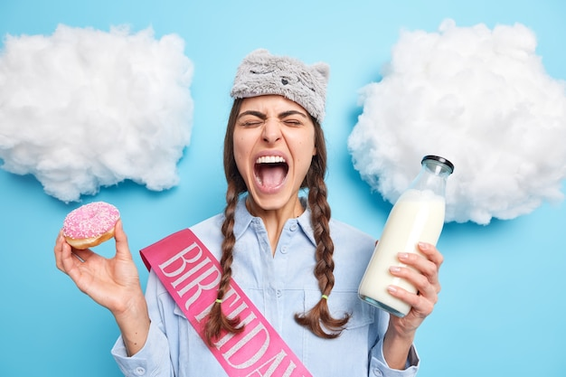 Woman exclaims loudly keeps mouth wide opened eats harmful junk food poses with sweet doughnut and milk dressed in domestic clothes poses indoor
