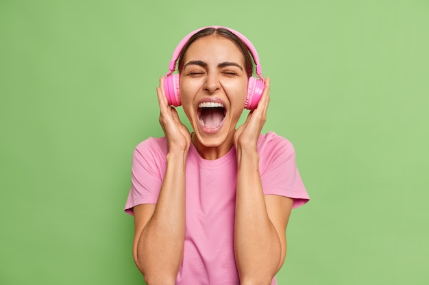 Woman exclaims loudly keeps mouth wide opened listens music with loud sound in headphones wears casual t shirt on green chills alone