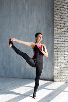 Женщина выполняет расширение ноги