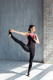 Woman executing an extended hand-to-big-toe yoga pose