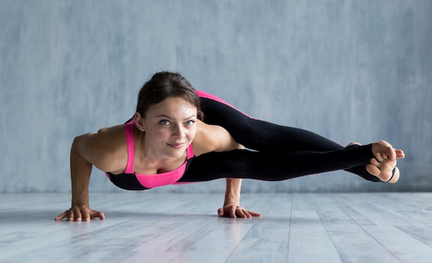 Woman executing a side crane pose while looking into the camera