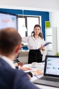 기업 직원을 위한 현대적인 사무실 회의실에서 재무 프레젠테이션을 하는 여성 임원 지도자 코치 발표자. 전문 스타트업 금융 사무실에서 일하는 다민족 기업인 d