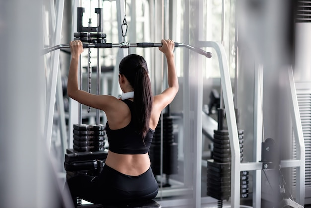 Woman exercise with lat pulldown machine in gym