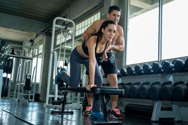 Женщина упражнения с тренером, молодая пара работает в тренажерном зале вместе.