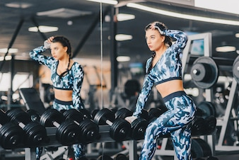Woman exercise workout in gym fitness breaking relax holding dumbbell