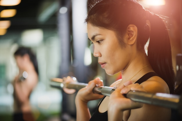 Woman exercises with barbell. fitness, bodybuilding, exercise and healthy lifestyle
