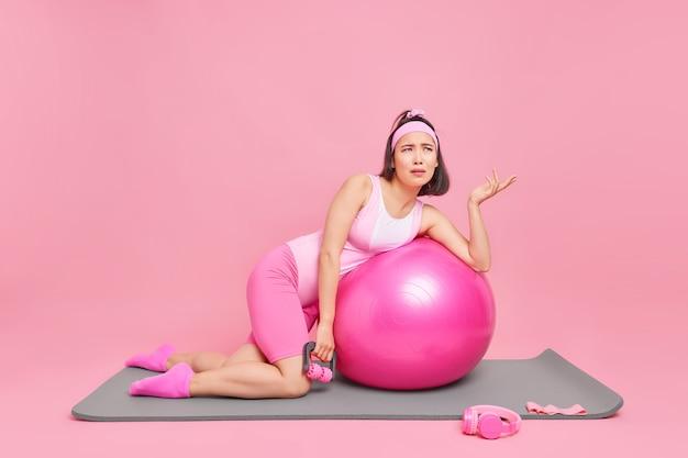 La donna si esercita con l'attrezzatura sportiva e la palla fitness solleva il palmo ha dispiaciuto l'espressione stanca posa sul tappetino sul muro rosa. sport domestici durante la quarantena