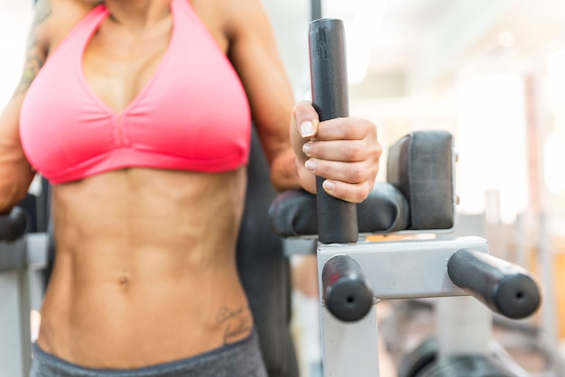 ジムで腹部を運動する女性。焦点は手にあります