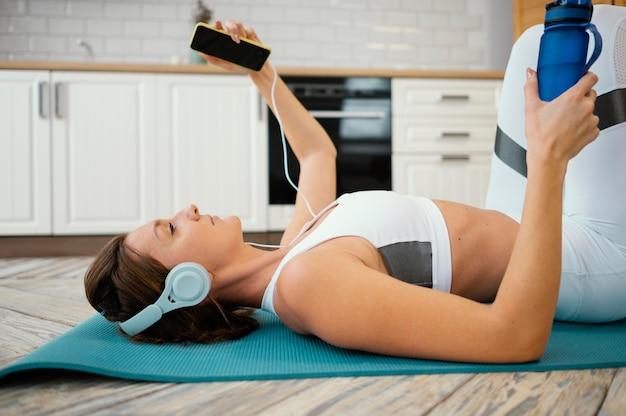 自宅で運動し、音楽を聴く女性