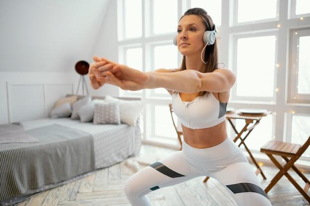 Женщина тренируется дома и слушает музыку