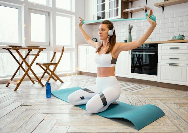 음악을 듣는 동안 집에서 운동하는 여자