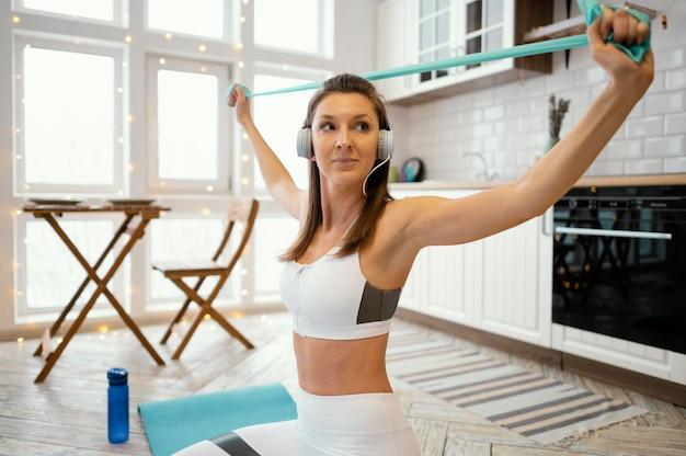 Женщина тренируется дома во время прослушивания музыки