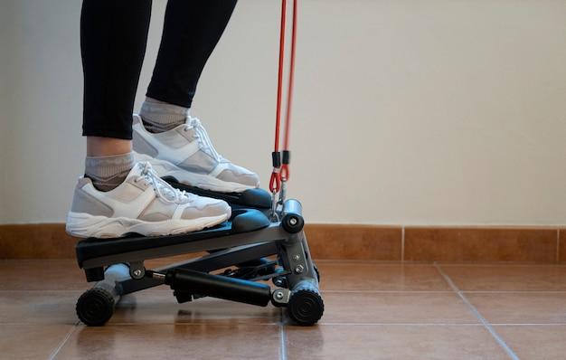 油圧ステップで自宅で運動する女性