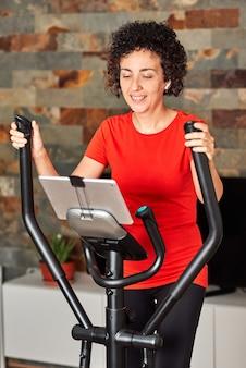 거실에서 디지털 태블릿을 보고 있는 온라인 교차 훈련 타원형 수업으로 집에서 운동하는 여성