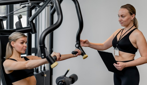 ジムで運動している女性とクリップボードを保持しているコーチ