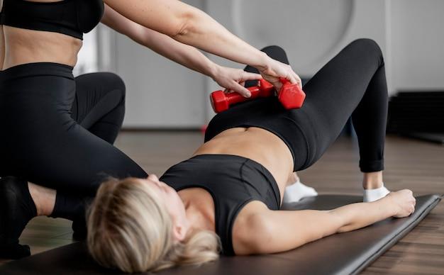 Женщина тренируется в тренажерном зале, поднимает бедра с гантелями