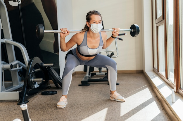 Женщина тренируется в тренажерном зале с оборудованием и медицинской маской
