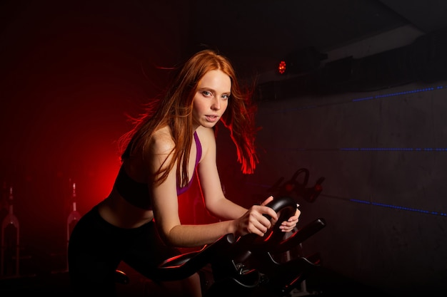 Woman exercising on bicycle at modern gym, workout woman training on smart stationary bike indoors in red neon lighted smoky space,