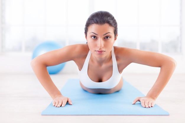 Женщина тренируется. уверенно молодая индийская женщина тренируется на коврике для йоги и смотрит в камеру