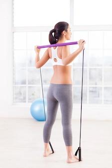 Женщина тренируется. полная длина вид сзади молодой женщины, тренирующейся в спортивном клубе