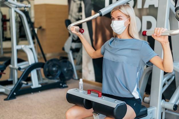 Donna che si esercita in palestra con maschera medica e attrezzature