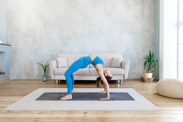 Woman exercising at home doing yoga stretching while standing in bridge pose at home