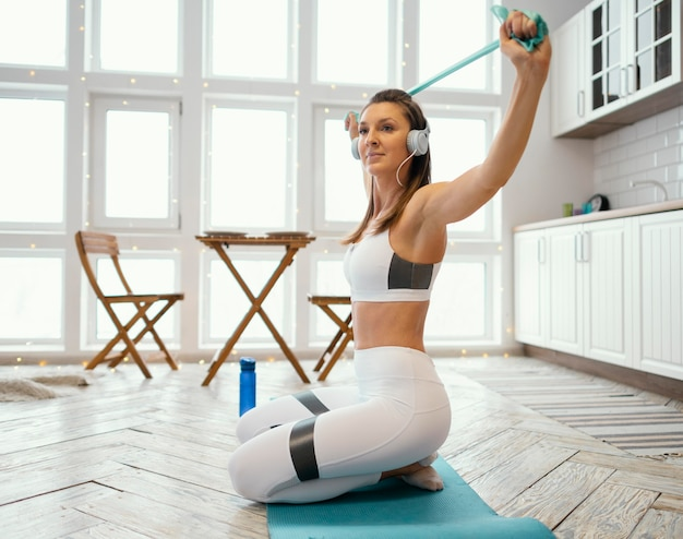 Woman exercising at home while listening music