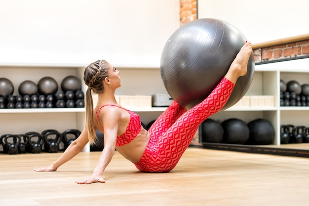 Woman exercising legs with gym ball