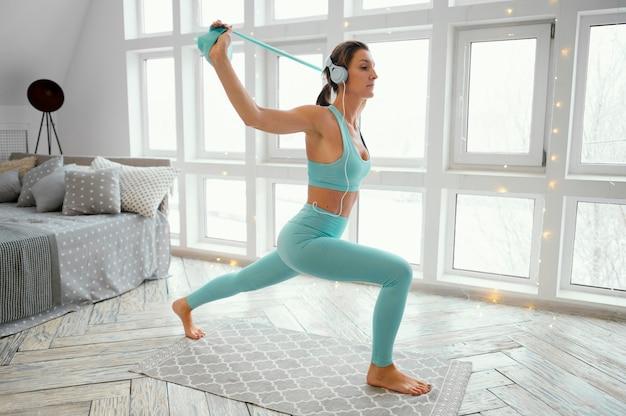 Donna che si esercita sulla stuoia con fascia elastica