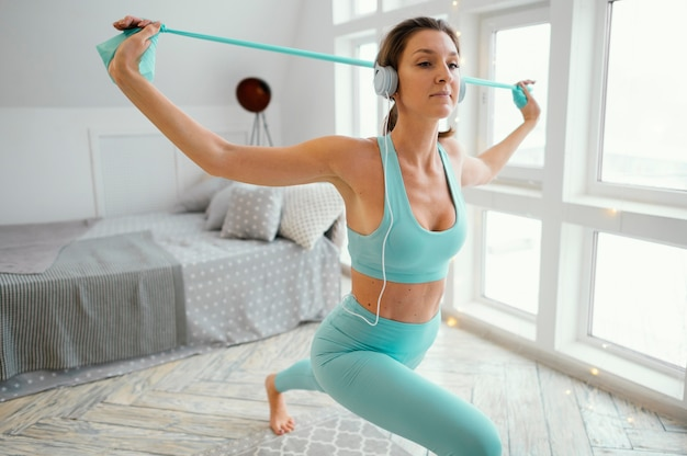 Woman exercising on mat with elastic band