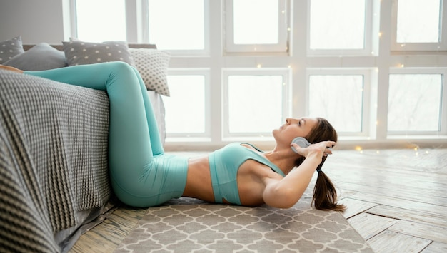 Женщина тренируется на коврике и слушает музыку